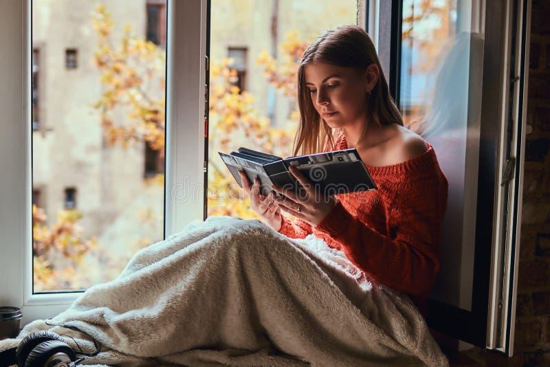 La giovane donna in un maglione caldo ha riguardato le sue gambe di coperta, esaminando l'album di foto, sedentesi sul davanzale immagini stock