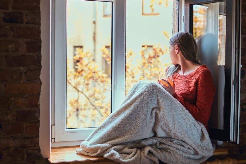 La giovane donna in un maglione caldo ha riguardato le sue gambe di coperta, rilassantesi con un vetro di succo, sedentesi sul da immagine stock