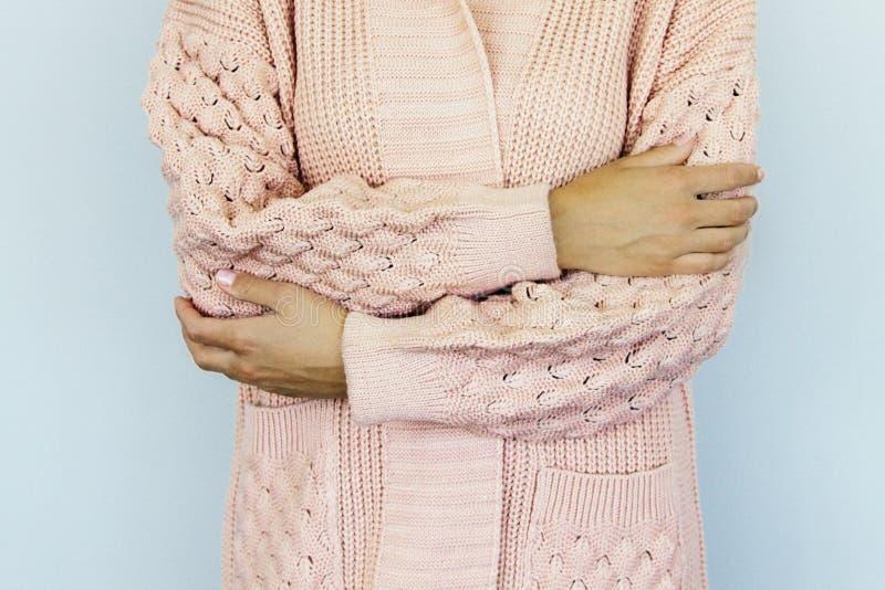 La giovane donna in un maglione tricottato caldo ha piegato le mani sulla cinghia immagine stock libera da diritti