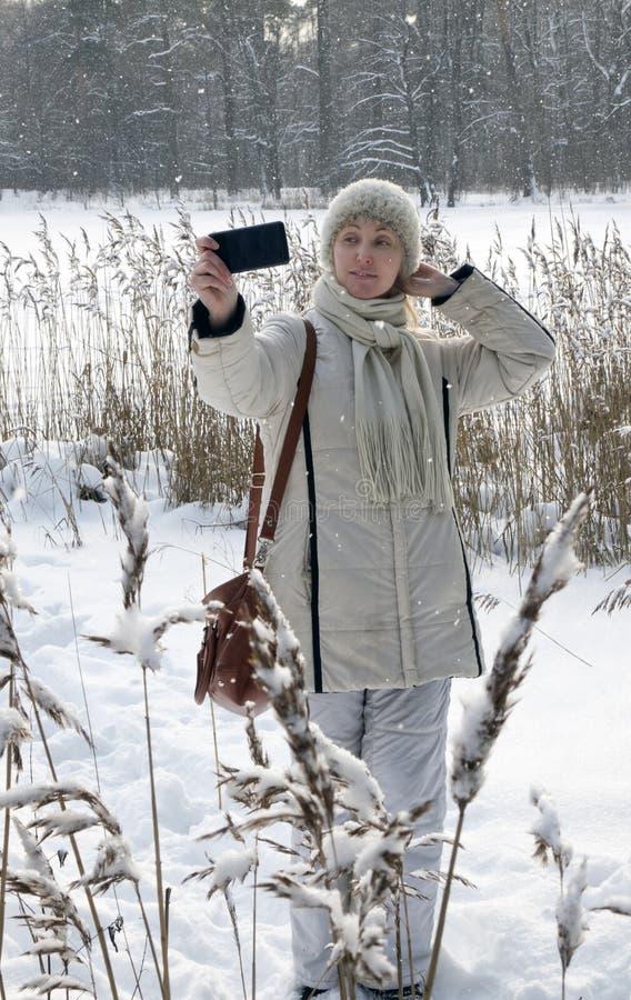 La giovane donna in un rivestimento bianco fa un selfie sulla costa del lago della foresta dell'inverno immagine stock libera da diritti