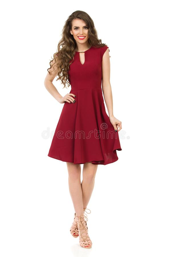 La giovane donna in vestito elegante da Borgogna sta camminando con la mano sull'anca immagine stock
