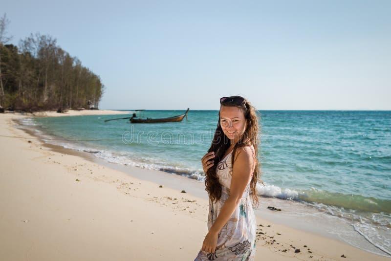 La giovane donna in vestito sta camminando sulla spiaggia sulla costa dell'oceano immagini stock libere da diritti