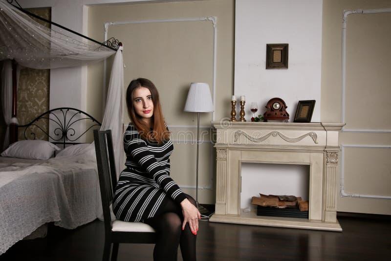 La giovane donna in vestito a strisce si siede su aChair fra la camera da letto di lusso immagini stock