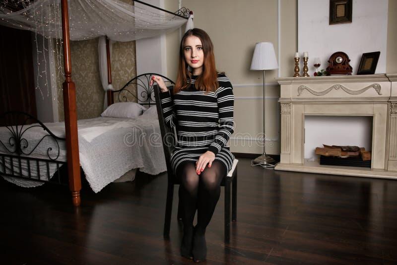 La giovane donna in vestito a strisce si siede su aChair fra la camera da letto di lusso fotografia stock