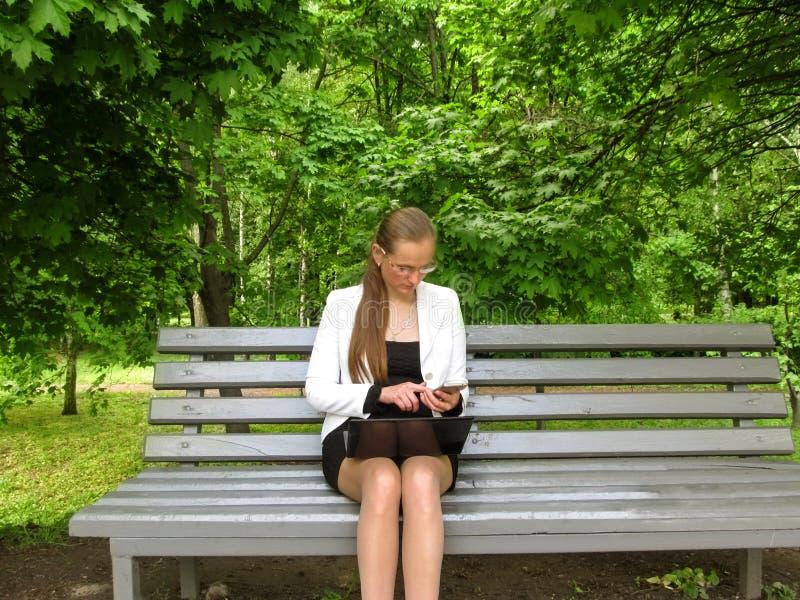 La giovane donna in vetri e vestiti dell'ufficio sta esaminando il telefono mentre si sedeva nel parco su un banco con un compute fotografie stock