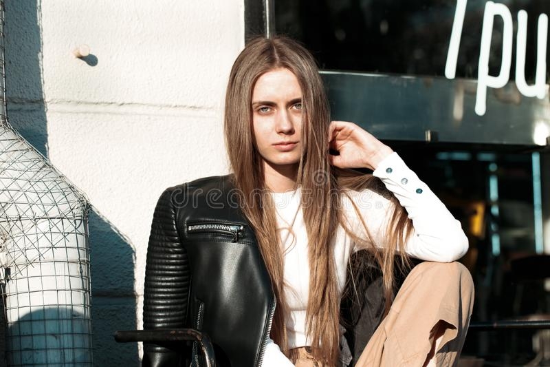 La giovane e bella donna sta sedendosi su un banco nella via e sta posando per la macchina fotografica immagini stock