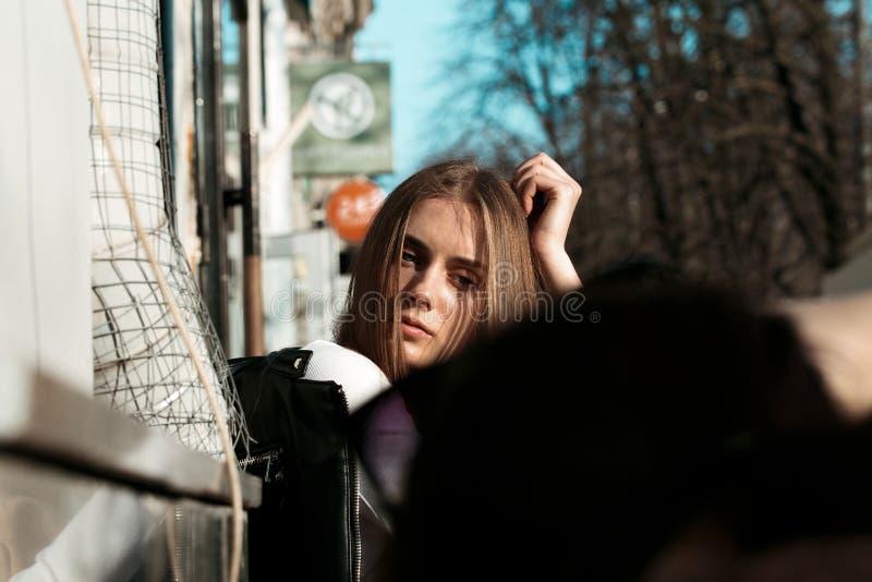 la giovane e bella donna sta sedendosi su un banco nella via e sta posando per la macchina fotografica fotografia stock libera da diritti