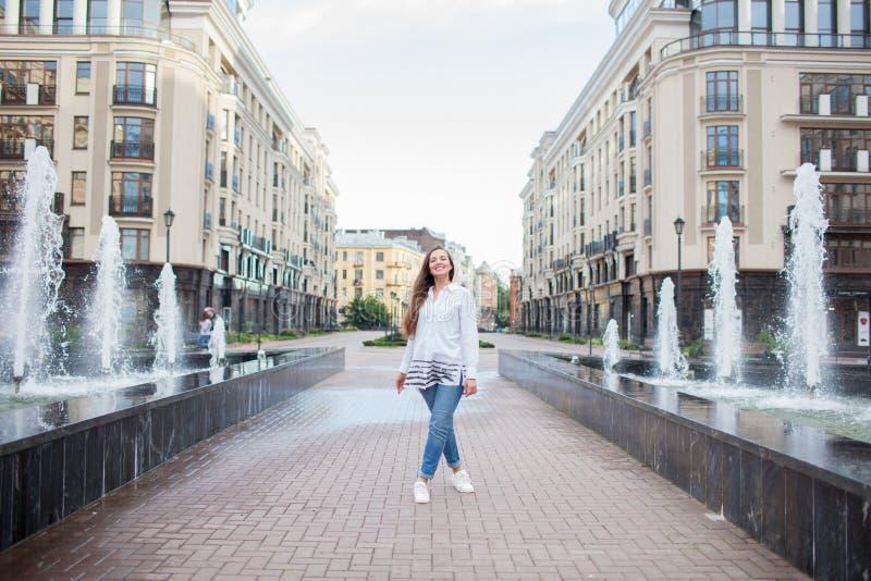La giovane e bella ragazza cammina la fontana e sorridendo in un nuovo complesso residenziale fotografia stock
