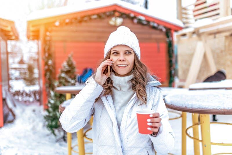 La giovane e bella ragazza sta chiamando dal telefono Nella città di inverno, nelle mani di una tazza del tè del caffè Smartphone fotografie stock