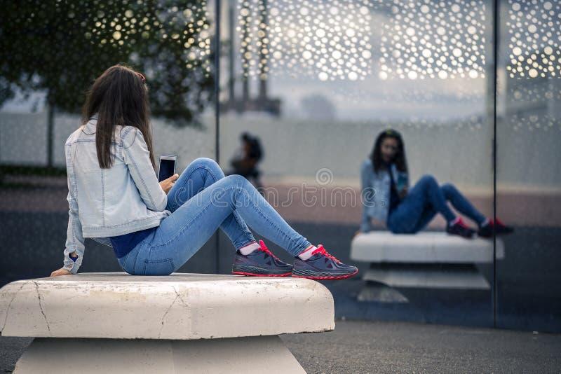 La giovane e donna attraente sta sedendosi sul banco in complesso industriale immagine stock libera da diritti