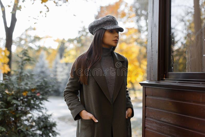 La giovane e ragazza alla moda attraente in un cappotto elegante grigio ed in un cappuccio d'annata grigio si rilassa all'aperto  fotografie stock