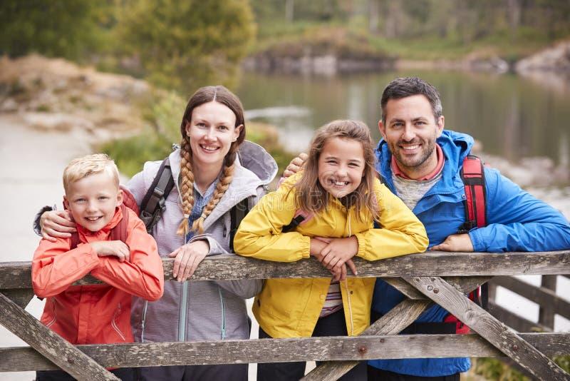 La giovane famiglia che si appoggia un di legno recinta la campagna, esaminante la macchina fotografica, fine su fotografia stock