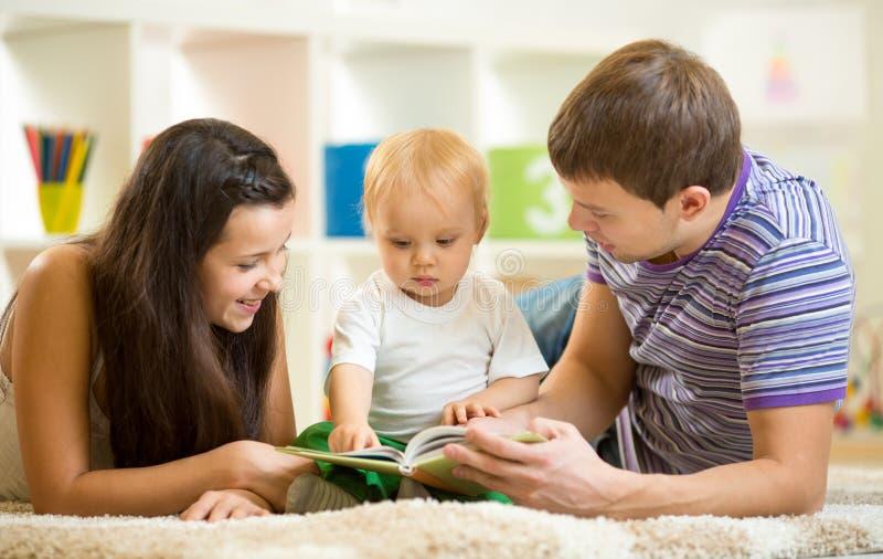 La giovane famiglia felice con il ragazzo del bambino ha letto il libro di bambini immagine stock