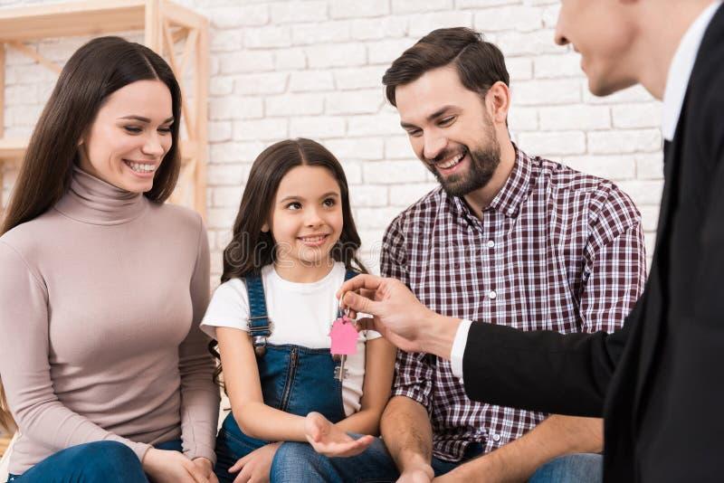 La giovane famiglia felice ottiene le chiavi alla nuova casa, che l'agente immobiliare ha contribuito a scegliere La famiglia com immagine stock libera da diritti
