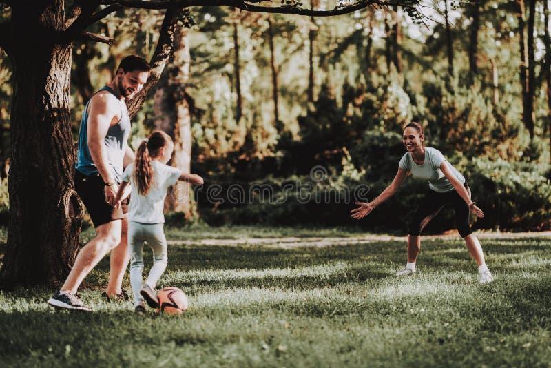 La giovane famiglia felice si diverte all'aperto nel parco dell'estate fotografia stock