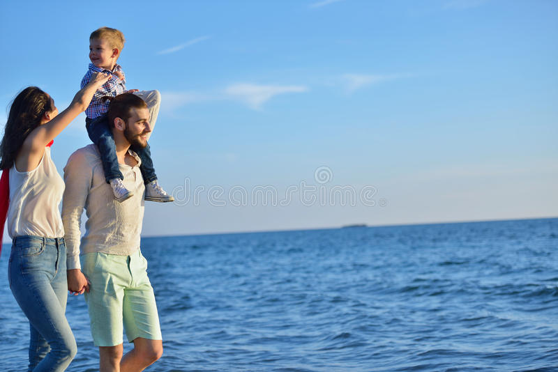 La giovane famiglia felice si diverte sulla spiaggia per funzionare e saltare al tramonto fotografie stock libere da diritti