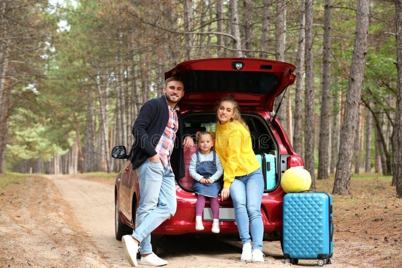 La giovane famiglia felice vicino al tronco di automobile ha caricato con le valigie immagini stock libere da diritti