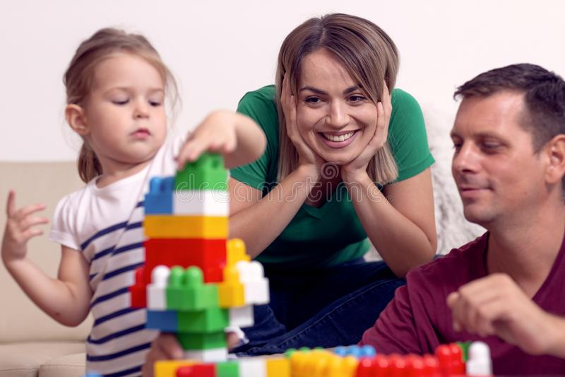 La giovane famiglia sta divertendosi il gioco con la figlia sveglia a casa fotografia stock