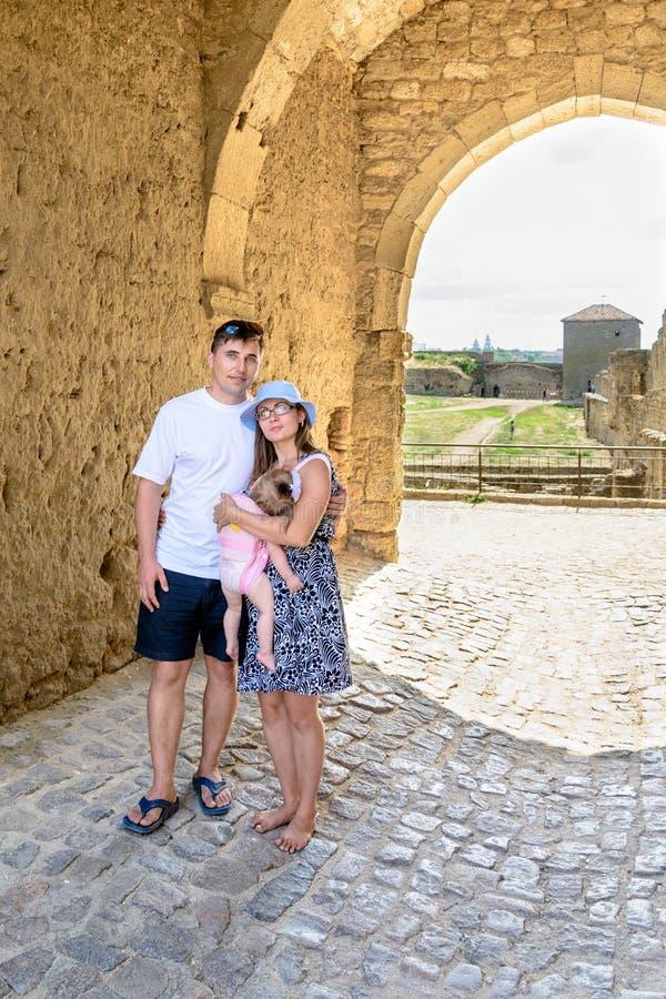 La giovane famiglia sta sui precedenti degli arché in un castello medievale fotografie stock