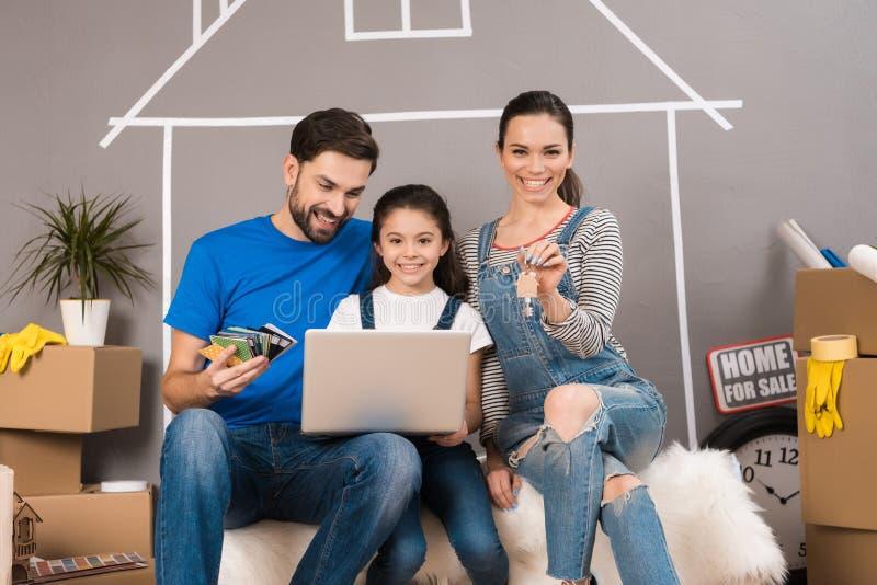 La giovane famiglia utilizza il computer portatile per annunciare della casa di vendita Concetto 6 del bene immobile immagini stock