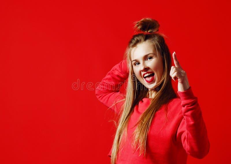 La giovane femmina graziosa ha capelli leggeri lunghi, sorriso piacevole, fa il gesto con il dito indice immagine stock libera da diritti
