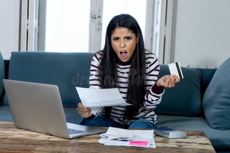 La giovane femmina infelice nelle attività bancarie di sforzo ed il debito di contabilità fatturano le spese ed i pagamenti delle immagine stock