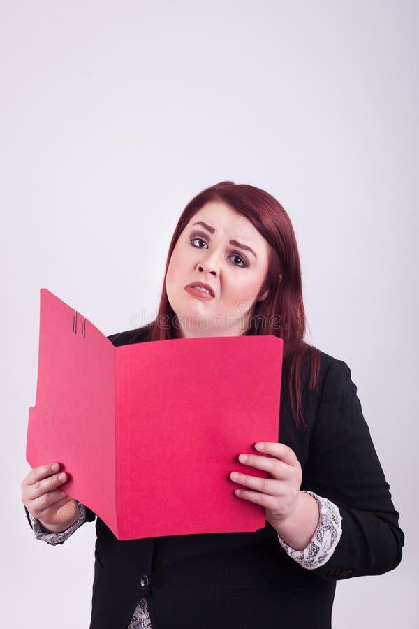 La giovane femmina professionale che giudica una cartella di archivio rossa aperta preoccupata ha sopraffatto l'espressione fotografia stock