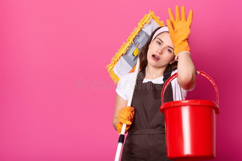 La giovane femmina stanca attraente tiene la mano sulla fronte, mette la zazzera sulla spalla Casalinga annoiata con il secchio e fotografia stock libera da diritti
