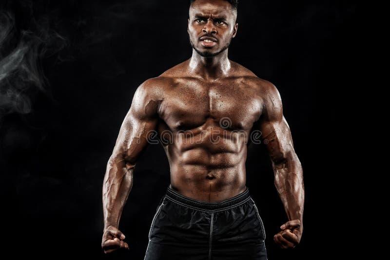 La giovane forma fisica muscolare mette in mostra l'allenamento dell'uomo con la testa di legno nella palestra di forma fisica immagini stock libere da diritti