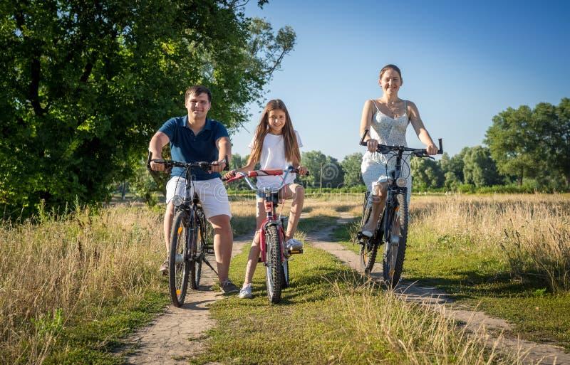 La giovane guida felice della famiglia va in bicicletta con il bambino nel campo immagini stock