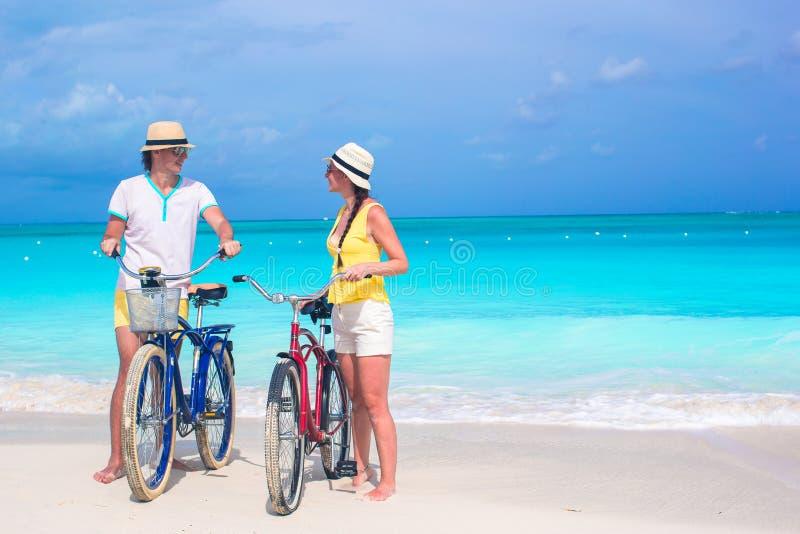 La giovane guida felice delle coppie bikes su tropicale bianco fotografia stock libera da diritti