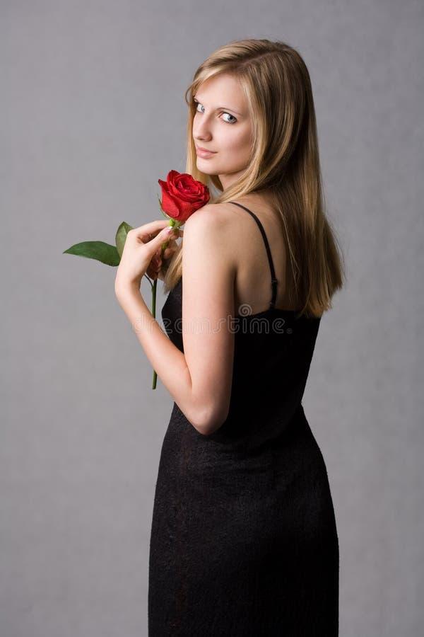 La giovane holding bionda splendida della donna è aumentato. fotografia stock libera da diritti