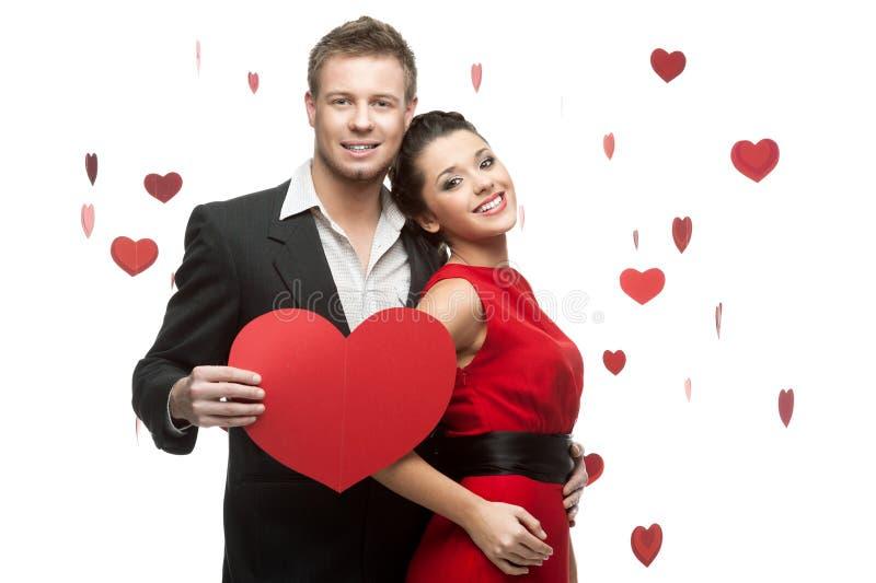 La giovane holding delle coppie firma dentro il modulo di cuore rosso immagini stock