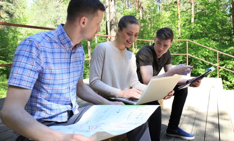 La giovane impresa, giovani creativi raggruppa il 'brainstorming' sulla riunione fuori dell'ufficio fotografia stock