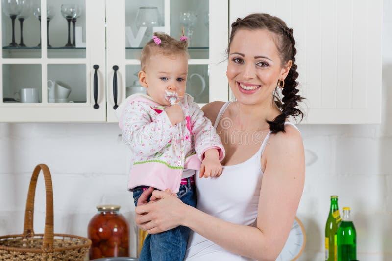 La giovane madre alimenta il bambino nella cucina. immagini stock libere da diritti