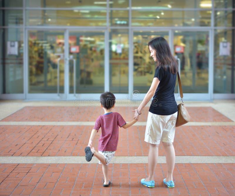 La giovane madre asiatica ed il suo bambino vanno a fare spese nel centro commerciale fotografie stock libere da diritti