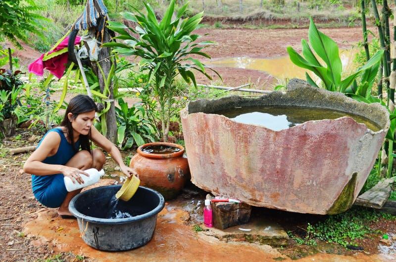 La giovane madre asiatica lava i piatti in cucina primitiva immagine stock