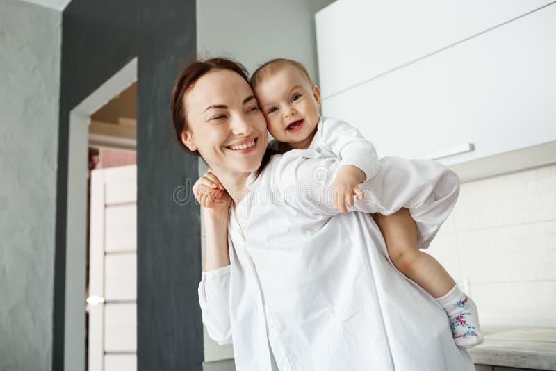 La giovane madre bella che gioca con il piccolo neonato che lo tiene sopra appoggia con le mani Bambino brightfully che sorride e immagine stock libera da diritti