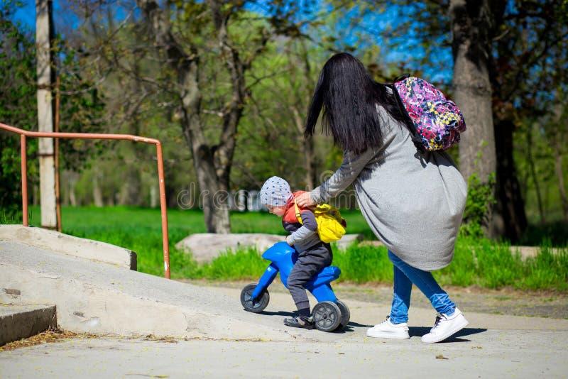 La giovane madre cammina con il piccolo figlio all'aperto con la motocicletta del ` s dei bambini fotografia stock libera da diritti