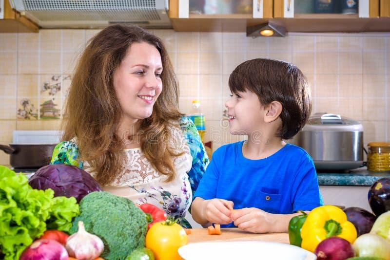 La giovane madre del cuoco che sta con il suo piccolo figlio nel kitche immagine stock libera da diritti