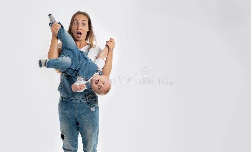 La giovane madre divertente tiene le sue gambe del neonato capovolte immagini stock
