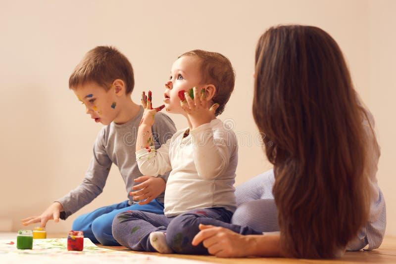 La giovane madre e suoi due piccoli i figli vestiti in vestiti domestici stanno sedendo sul pavimento di legno nella stanza e nel fotografia stock