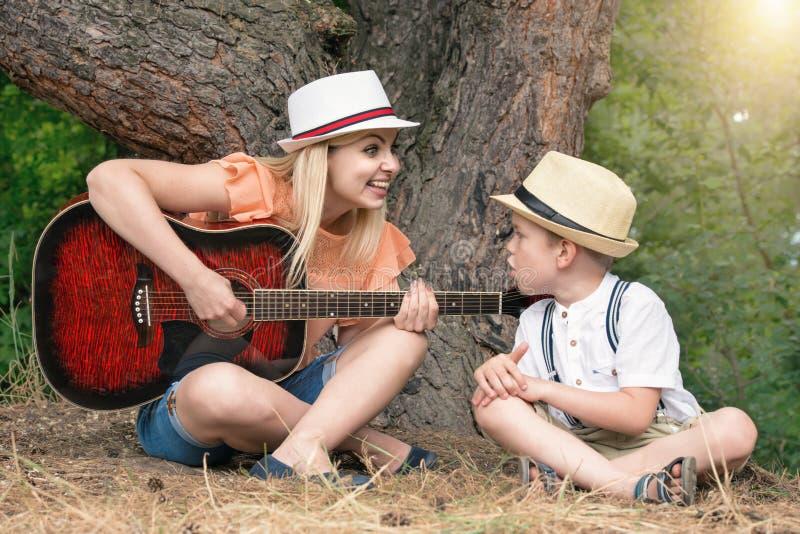 La giovane madre ed il bello resto del figlio nella foresta, cantano le canzoni sotto una chitarra fotografie stock libere da diritti