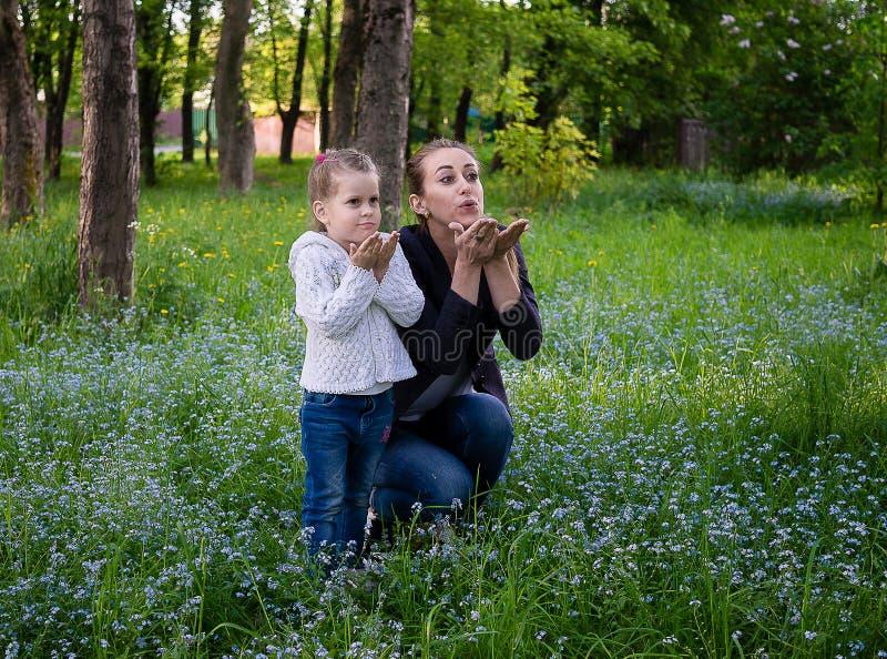 La giovane madre esile e la figlia di cinque anni inviano un bacio fotografie stock