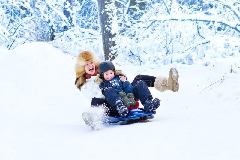 La giovane madre felice ed suo figlio sulla slitta guidano immagini stock libere da diritti