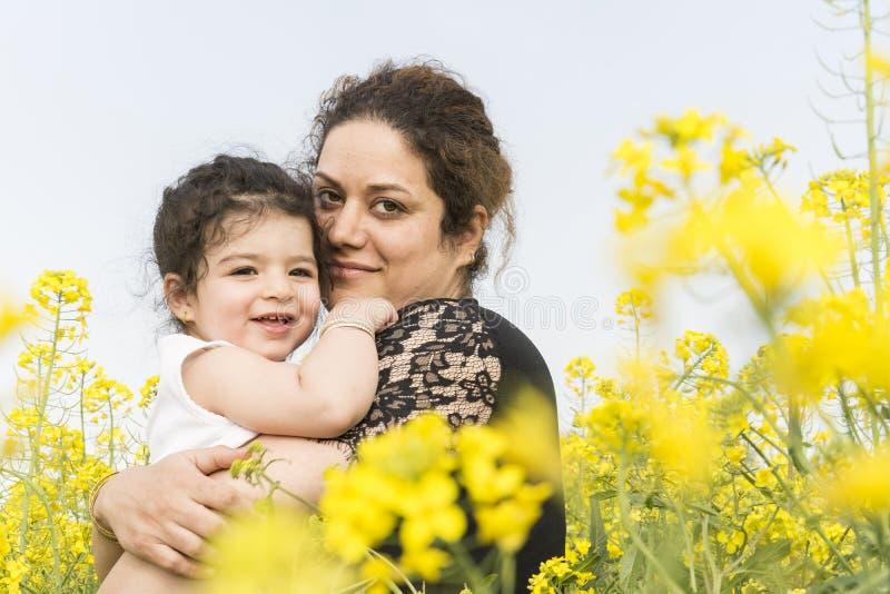 La giovane madre felice ha abbracciato la sua bambina sveglia al giacimento del canola fotografie stock libere da diritti