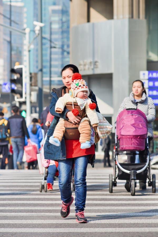 La giovane madre porta il suo bambino sul passaggio pedonale, Shanghai, Cina immagine stock libera da diritti