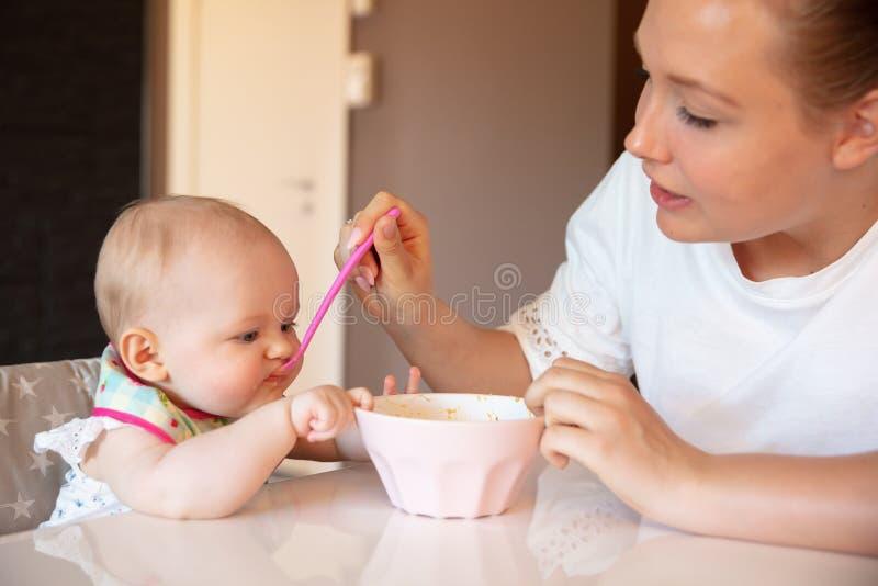 La giovane madre preoccupantesi alimenta la sua neonata fotografie stock libere da diritti