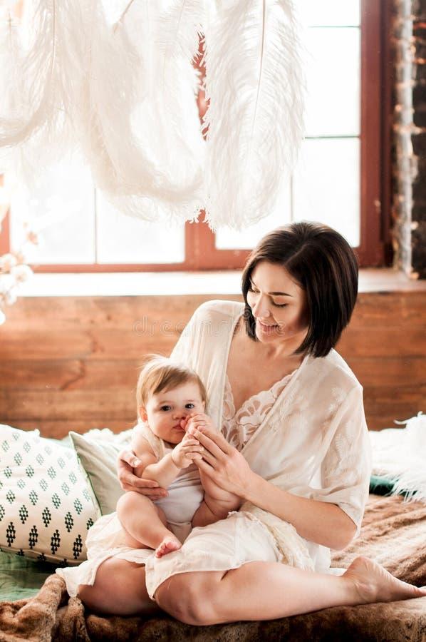 La giovane madre si siede sul letto con la sua piccola figlia di fronte alla finestra fotografia stock libera da diritti