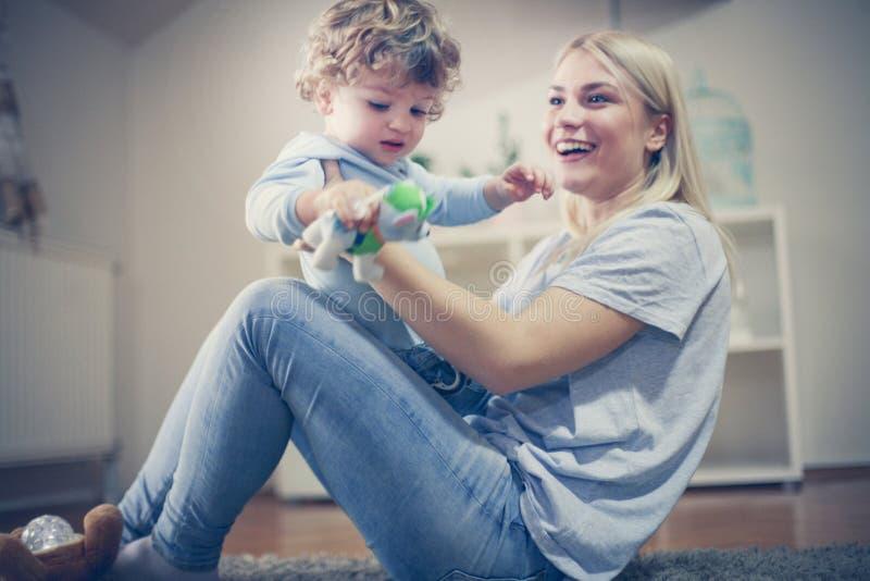 La giovane madre sorridente ha gioco con suo figlio immagini stock
